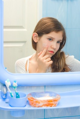 Girl looking in mirror at pimple